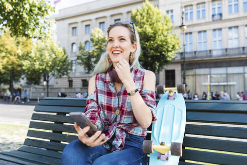 Portrait of smiling young woman sitting on bench with skateboard and mobile phone - WPEF02204