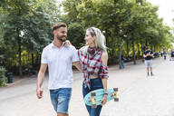 Happy young couple walking in a park - WPEF02219