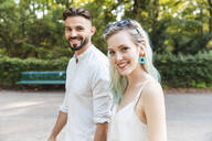 Portrait of happy young couple walking in a park - WPEF02225