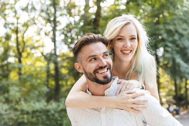 Portrait of happy young man giving his girlfriend a piggyback ride - WPEF02228