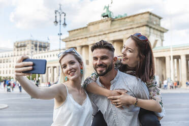 Portrait of three friends taking selfie with cell phone in front of Brandenburger Tor, Berlin, Germany - WPEF02234