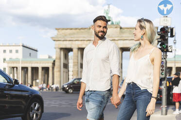 Happy young couple walking hand in hand in front of Brandenburger Tor, Berlin, Germany - WPEF02237
