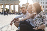 Three happy friends sitting near  Brandenburger Tor looking at cell phone, Berlin, Germany - WPEF02240