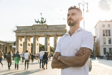 Portrait of young man standing in front of Brandenburger Tor at backlight, Berlin, Germany - WPEF02243