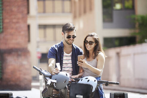 Young couple using smart phone while standing with bicycles - CAVF66770
