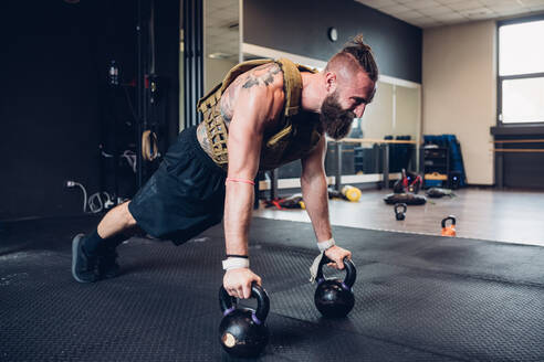 Young tattooed man training in gym, doing push ups on kettle bells - CUF52933