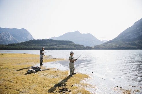 Mother and son fishing at sunny, scenic lakeside - HEROF39679
