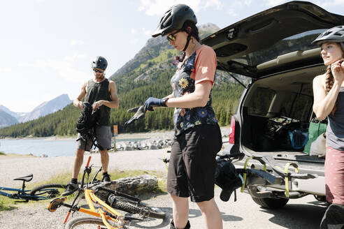 Friends preparing for mountain biking in sunny parking lot at lakeside - HEROF39742