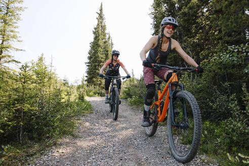 Women mountain biking on trail in woods - HEROF39745