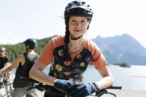 Portrait confident woman mountain biking at sunny lakeside - HEROF39751