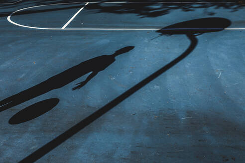 Shadow of a basketball player on a court at noon - CAVF67273