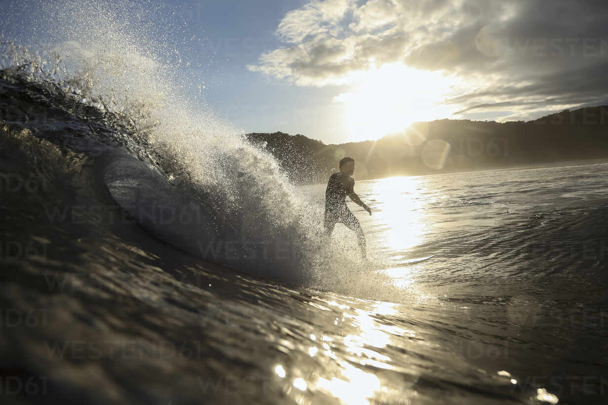 Surfer on a wave at sunset time - CAVF67339 - Cavan Images/Westend61