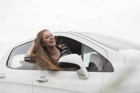 Cheerful woman peeking out from car window against clear sky - CAVF67417