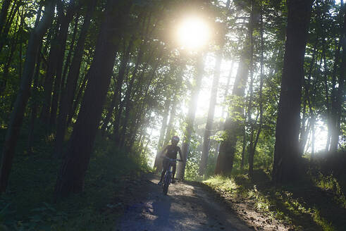 Girl riding bicycle on dirt road in forest - CAVF67462