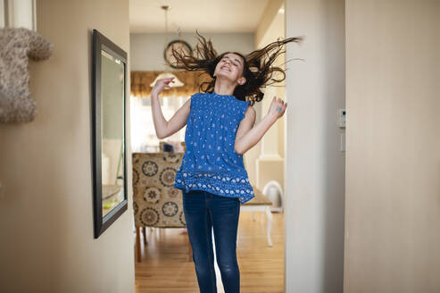 Teen girl jumping and flipping her hair in front of mirror at home - CAVF67629