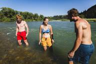 Happy friends enjoying in lake against clear sky - CAVF67680