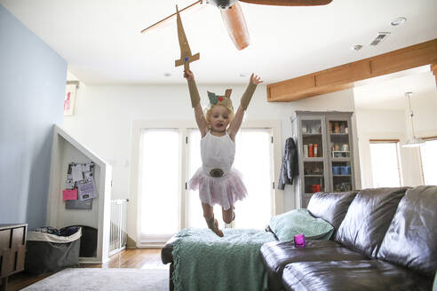 Girl with crown and sword jumping from sofa at home - CAVF67755