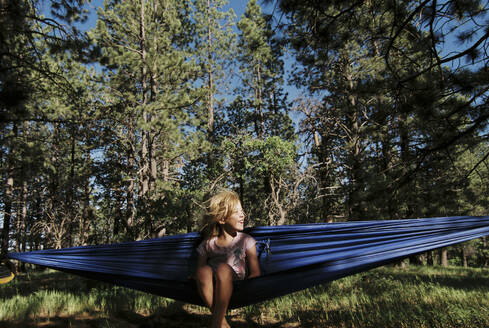Cheerful girl resting in hammock against trees at forest - CAVF67864
