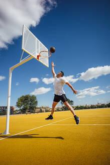 Man playing basketball on yellow court, dunking - OCMF00846