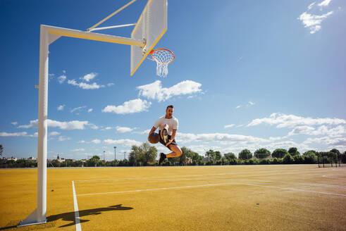 Man playing basketball on yellow court, dunking - OCMF00849