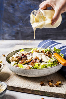 Hand of person pouring dressing over bowl of Caesar salad with romaine lettuce, Parmesancheese, bacon, chicken breast and croutons - SBDF04080