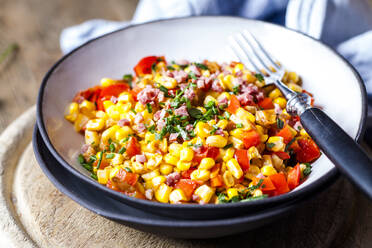 Bowl of warm corn salad with bell pepper, potatoes and diced ham - SBDF04083