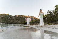 Happy mother walking with daughter on the beach - DIGF08726