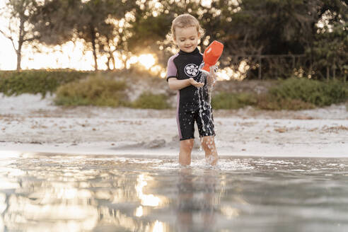 Cute toddler girl playing with watering can in the sea - DIGF08732
