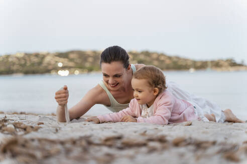 Happy mother and daughter playing with sand on the beach - DIGF08738