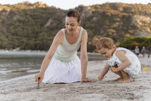 Mother and daughter drawing with little sticks in sand on the beach - DIGF08750
