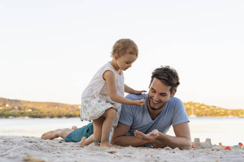 Father and daughter lying on the beach - DIGF08756