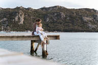 Mother with daughter sitting on a jetty at sunset - DIGF08777