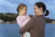 Happy mother carrying her daughter on a jetty at sunset - DIGF08783
