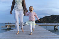 Happy girl walking with mother on a jetty at sunset - DIGF08789