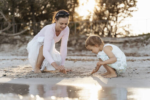Happy mother with daughter playing with sand on the beach - DIGF08795