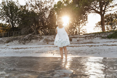 Cute toddler girl standing on the beach at sunset - DIGF08798
