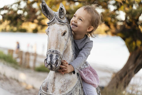 Happy cute toddler girl sitting on wooden horse - DIGF08804