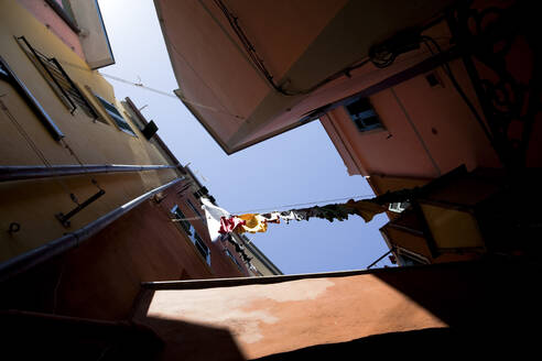 Worm's eye view of laundry hanging out to dry in Manarola, Cinque Terre, Italy - GIOF07403