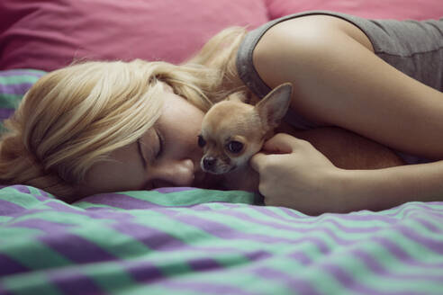Teenage girl with Chihuahua lying on bed - CAVF68106