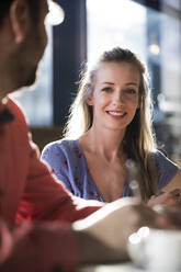 Porrait of smiling woman with man in a cafe - FKF03701