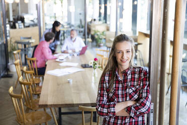 Portrait of casual businesswoman in a cafe with colleagues having a meeting in background - FKF03713