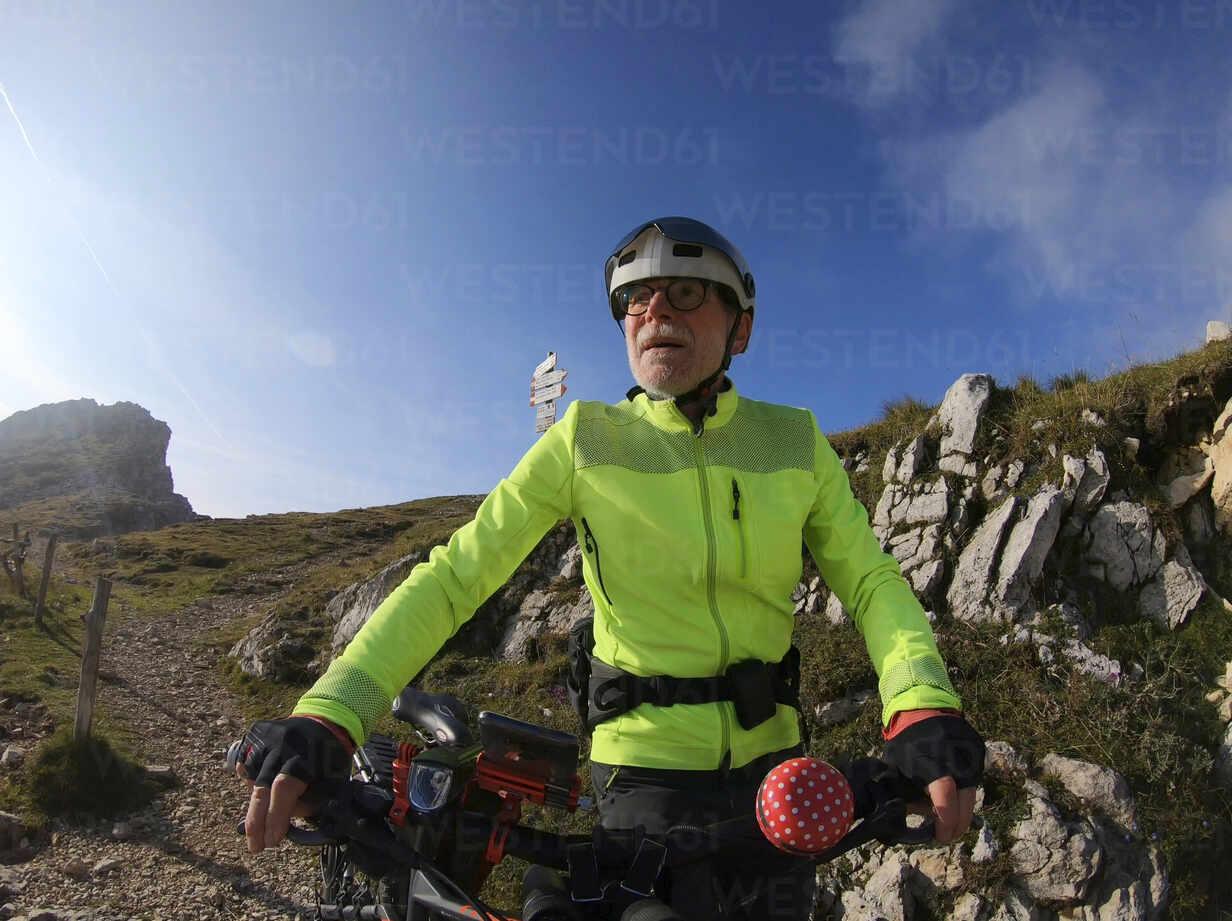 Senior man riding e-bike in nature - LAF02391 - Albrecht Weißer/Westend61