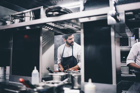 Cook at work in a restaurant kitchen - OCMF00854