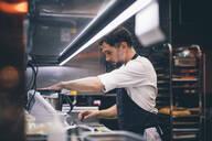 Cook at work in a restaurant kitchen - OCMF00860