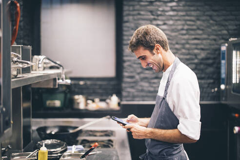 Smiling cook using smartphone in the kitchen of a restaurant - OCMF00866