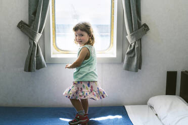Portrait of little girl standing on bed of ship's cabin in front of window - GEMF03254