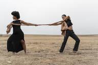 Two women pulling a cloth in bleak landscape - ERRF01958