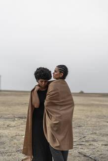 Two women standing in bleak landscape sharing blanket - ERRF01967