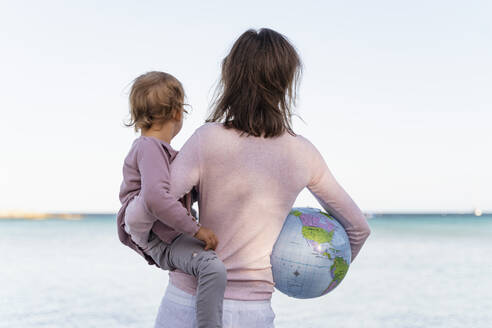 Back view of woman holding little daughter and Earth beach ball looking at horizon - DIGF08827