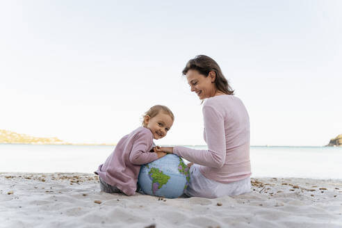 Portrait of happy little girl sitting with her mother on the beach playing with Earth beach ball - DIGF08830